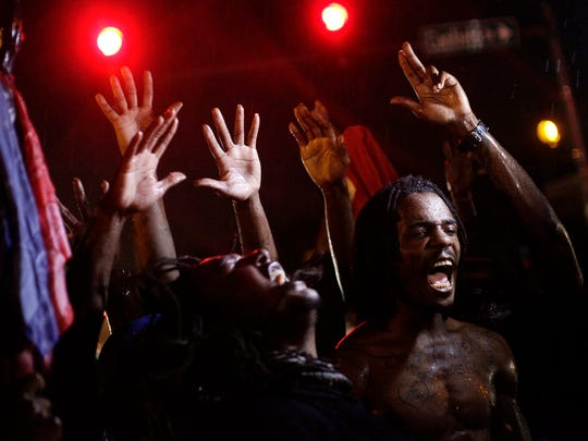 Demonstrators protest against the Aug. 9 police shooting of  Michael Brown by holding their hands up while gathered on the streets of Ferguson, Mo., on Aug.16, 2014.