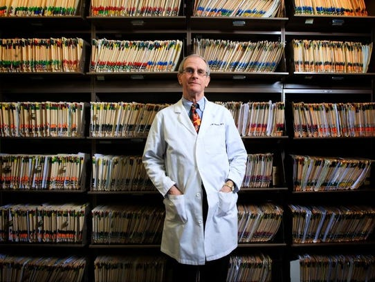 Dr. John Weeter, a plastic surgeon, stands among his