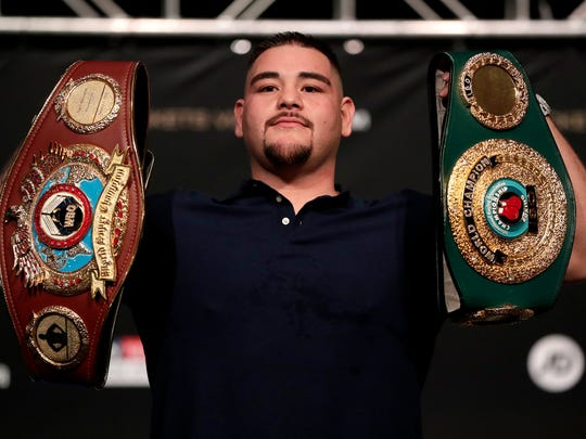 Andy Ruiz holds a couple of Anthony Joshua's belts while posing for photographs during a press conference ahead of their heavyweight bout, Thursday, May 30, 2019, in New York. Joshua will defend his WBA, WBO and IBF heavyweight titles. (AP Photo/Julio Cortez)
