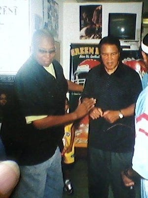 The late Jonathan Burney, left, helps the late Muhammad Ali into a chair at the Hair Unlimited Barbershop between 2002 and 2006.