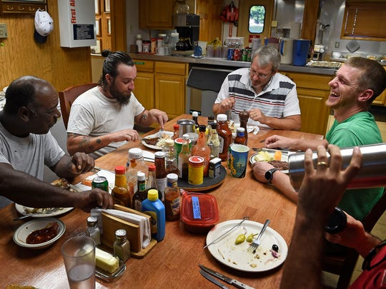 David Miget, right, laughs as he eats lunch with Capt. Todd Butts, center, and other crew members Terry George, left, and Nick Willis. With around-the-clock schedules, it's hard for members of the crew aboard the James Paul Ayers Ingram towboat to eat get together. But they try.