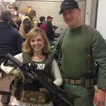 Amber Pinski learns how to walk with Officer Scott Bambenek's HRU firearm during the Citizens' Academy presentation.