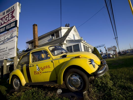 A yellow Volkswagen Beetle sits outside Earl Bradley's