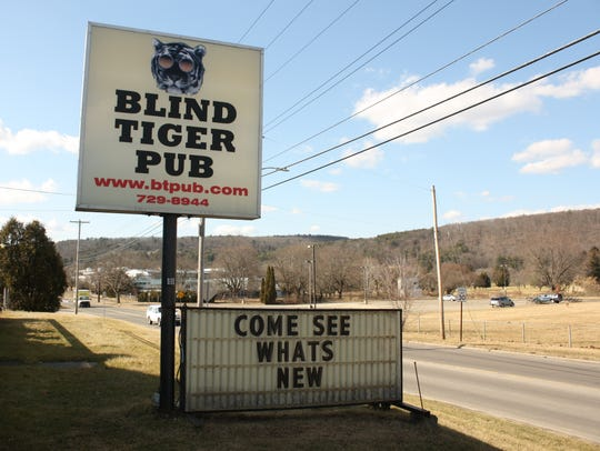 """A sign outside the Blind Tiger Pub reads """"come see what's new."""""""