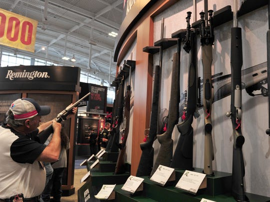 A convention attendee looks at a Remington bolt action rifle at the 2015 NRA Annual Convention in Nashville, Tenn. April 10, 2015.