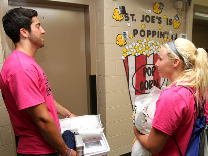 Michael Rotando, Point Pleasant and Lizzy Kroom, 18, Bayville,   help students move in at Georgian Court University in Lakewood.  The predominantly  all-girls school has recently started to admit boys and now has coed dorms. Wednesday August 21, 2014. Photo by Robert Ward