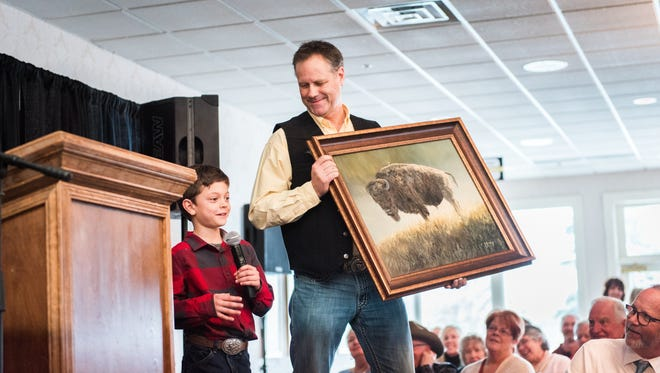 Artist Joe Kroneberg gets an assist from Jack Zabel during the Art in Action auction Friday. Jack drew the original buffalo on the canvas and helped with grass, Kroneberg told bidders.