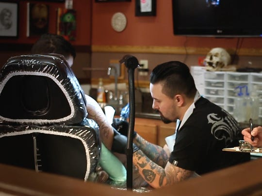 Laura Brusky, registered sanitarian for the Cascade City-County Health Department, inspects Pablo Jara at Level Up Tattoo in Great Falls.
