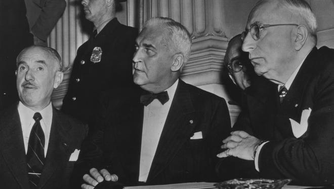 Jack Warner of Warner Bros., (from left); Paul V. McNutt, chief counsel for the movie industry; and Louis B. Mayer of Metro-Goldwyn-Mayer listen to a statement by Rep. J. Parnell Thomas (R-N.J.) (not shown) at the opening of a House Un-American Activities Committee inquiry into communist activities in the motion picture industry on Oct. 20, 1947.