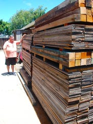 Jeffrey Priddy stands next to stacks of used redwood