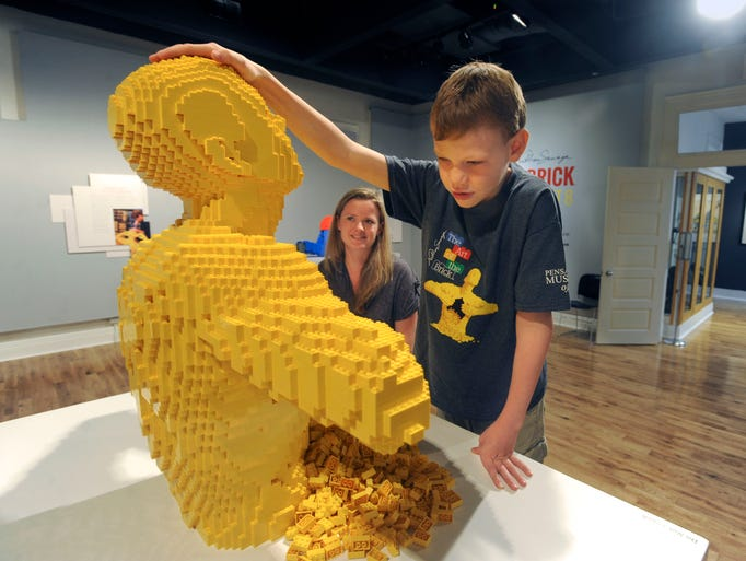 """Corbin Thornbury,10, who has been blind since birth, examines one of the art pieces Saturday morning at the the """"Art of the Brick"""" Lego exhibit as Cortlandt Glover, Director of Education at the Pensacola Museum of Art looks on. Artist Nathan Sawaya was contacted and told Nathan's story and gave permission for Nathan to touch the art."""