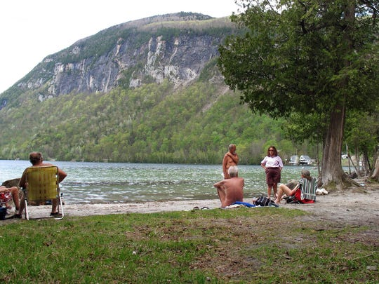People relax at the clothing-optional beach known as the Southwest Cove of Lake Willoughby in Westmore on May 18, 2017. Located on state land, state officials said the area, which also includes hiking trails, gets so much use in the summer that upgrades need to be made the protect the area from over use. Beach users are opposed to the plan because they think it could threaten their ability to use the area.