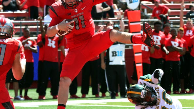 Rutgers quarterback Hayden Rettig leaps over a Norfolk's Sandy Chapman to score a touchdown in college football in Piscataway.