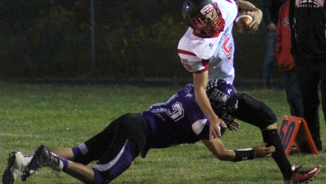 Mescalero's Harry Wheeler, left, tries to bring down Mountainair's Kaysey Reese on Friday night at Chiefs Stadium.
