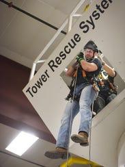 Field technician David Hoodenpyl repels from a 24 foot