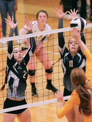 T.L. Hanna's Gabby Easton, left, and Hannah Burdette defend a spike by Greenwood's Liz Reese during the third set at T.L. Hanna High School in Anderson.