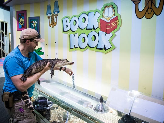 Chris Horner takes Blue out of his enclosure in the Book Nook at the Muncie Children's Museum in 2016.