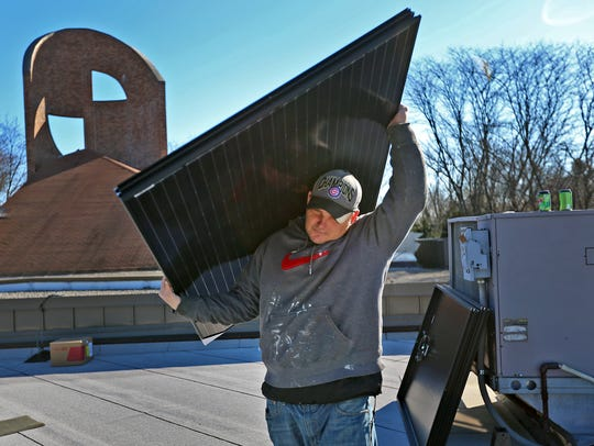 TJ Swan, with Rectify Solar, carries a solar panel