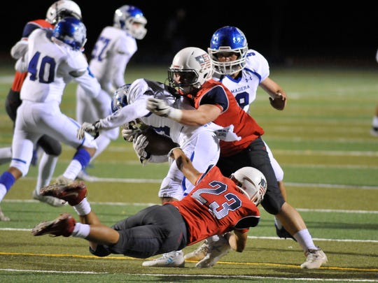 Edward Diaz dives to take down Madera in a Central Section Division III quarterfinal high school football game between Madera (6-5) and Tulare Western (9-1) at Bob Mathias Stadium on November 16, 2017.