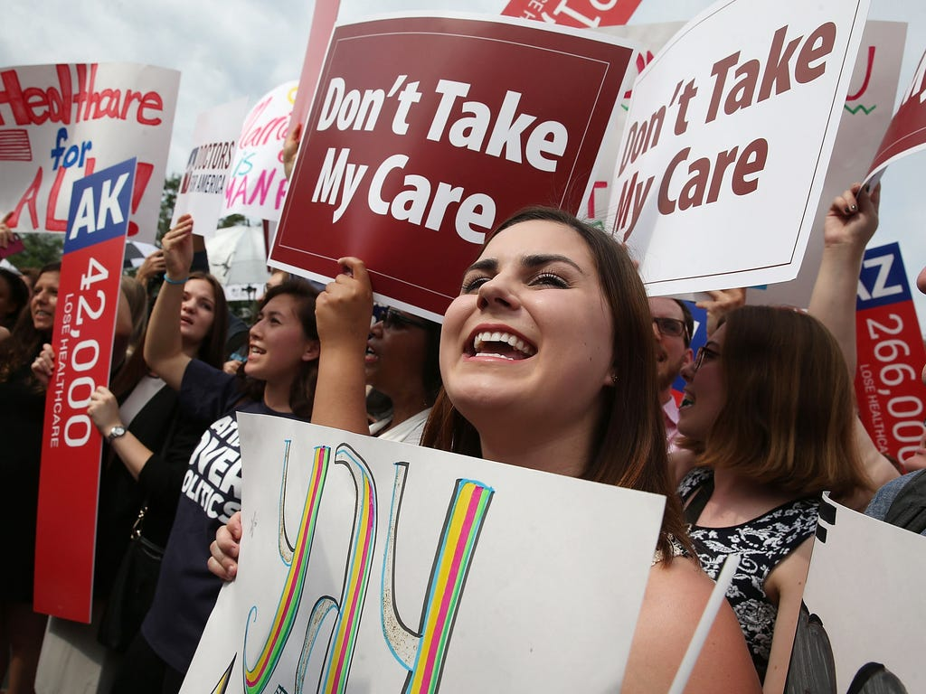 People cheer in front of the U.S. Supreme Court in Washington after the ruling was announced on the Affordable Care Act. The high court ruled that insurance subsidies created by the law can be offered in both state and federal health care exchanges t