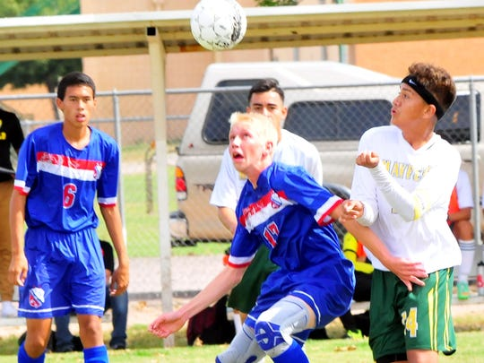 Las Cruces High's Lucas Kirby, middle, and Mayfield's Jonathon De La Cruz go up for a header attempt during Saturday's action at Field of Dreams.