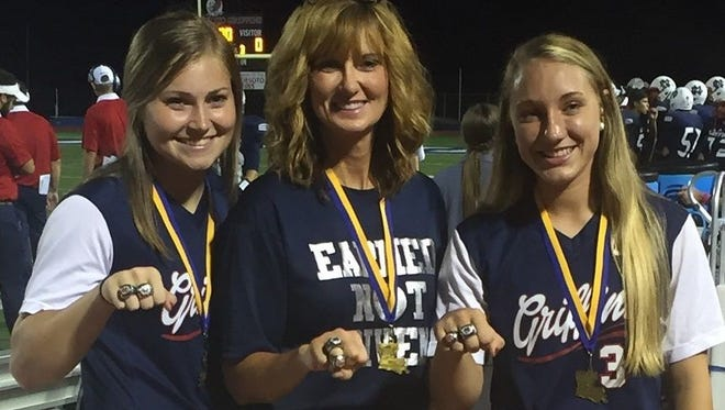North DeSoto pitcher Emma Callie Delafield, coach Lori McFerren and shortstop Bayli Simon display their Class 4A softball championship rings.