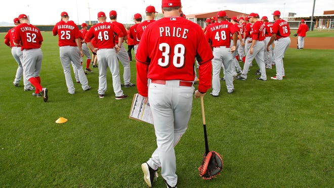 Reds manager Bryan Price looks on as pitchers and catchers stretch and warm up on Monday in Goodyear.