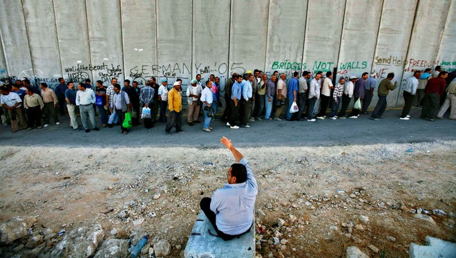 In this 2006 file photo, Palestinian workers stand in line next to Israel's separation barrier as they wait to cross a checkpoint into Jerusalem.