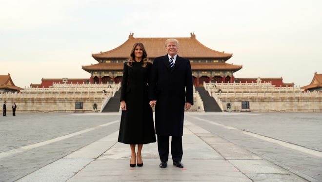 President Donald Trump (right) and first lady Melania Trump pose for a photo as they tour the Forbidden City on Wednesday in Beijing, China.