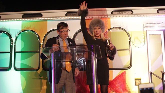 """Palm Springs Mayor Robert Moon and Suzanne Somers toast to the one year anniversary of the """"Buzz"""" bus in downtown Palm Springs."""