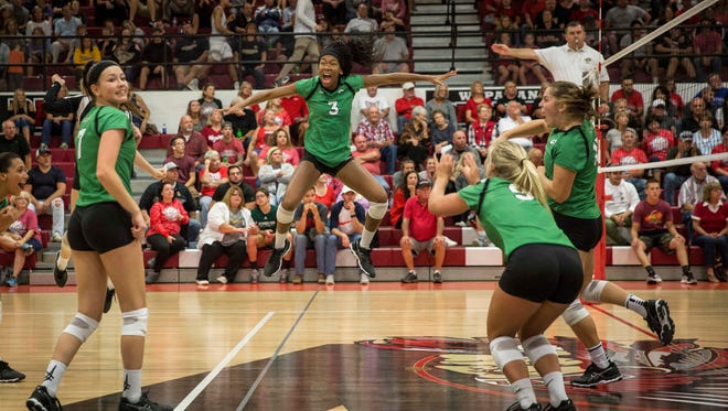 Yorktown's Courtney Watkins jumps into the air after beating Wapahani in the the Delaware County Volleyball Tournament on Sept. 28 at Wapahani High School. Yorktown won the game 3-1.