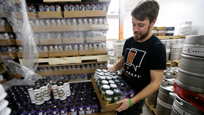 Henry Schwartz, founder and CEO of MobCraft, stacks beers in the brewery's cooler area.