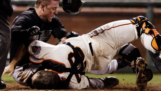 Marlins' Scott Cousins, top, collides with Giants catcher Buster Posey at home plate in 2010.