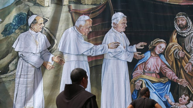 People examine a giant banner featuring the birth of Jesus with, from left, former Popes Paul VI, Jean-Paul II and Benedict XVI visiting him, on Friday at Manger Square outside the church of Nativity — revered as the site of Jesus' birth — in the West Bank city of Bethlehem.