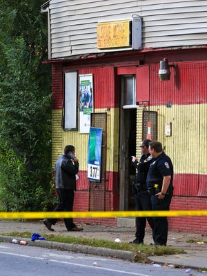 Louisville police stand outside the Save More convenience store in the 1200 block of West Hill Street. Two people were found shot in the Parkway Place housing complex while one was shot in the Save More convenience store across the street. The shootings were reported at 3:24 p.m.