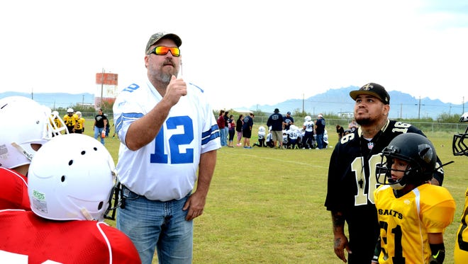 """At left, Charles """"Tink"""" Jackson, Luna County manager, flips the coin to open a Luna County Youth Football League game. Coach and league commissioner, Cesar Moreno, looks on."""