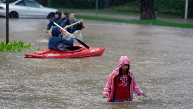 A girl wades through a flooded parking lot at a shopping center in Healdsburg, Calif.