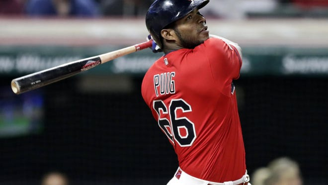 The Cleveland Indians' Yasiel Puig watches his ball after hitting a game-winning RBI-single in the 10th inning in a game against the Detroit Tigers on Sept. 18, 2019, in Cleveland. The Indians won 2-1 in 10 innings.  Puig had reached an agreement with Atlanta to play for the Braves this season but announced Friday that he has tested positive for COVID-19.
