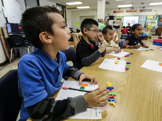 Fidel Garcia listens as Patty Hannon, a Billingual Associate Instructor at Slaughter Elementary, works with them on segmentation, deletion, vowels, and consonants. April 1, 2016