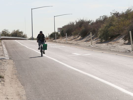 A cyclist rides on the shoulder of the Dillon Road