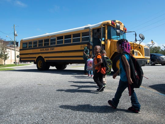 Head Start teacher, Whitney Henderson, left escorts her students to a waiting bus for a ride home from school Friday afternoon. The Head Start program has a fleet of buses that is old and unreliable. Many of its buses are often out of service, making it difficult for the organization to get students to and from its programs.