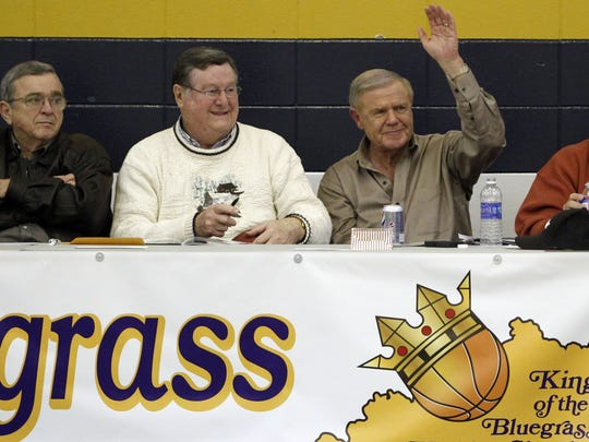 Former University of Kentucky coach Joe Hall (L) and former University of Louisville coach Denny Crum (R) wave to the crowd during the the King of the Bluegrass basketball tournament at Fairdale High School in Louisville, Kentucky.        December 20, 2012