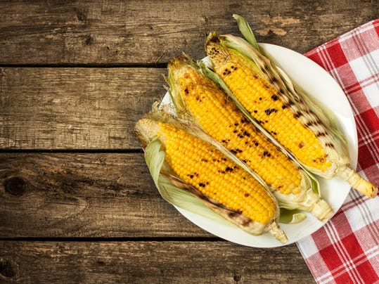 Grilled corn cobs on white plate, vintage wood as background