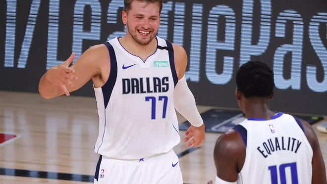 Dallas star Luka Doncic (77) celebrating a 3-point basket with teammate Dorian Finney-Smith against Milwaukee, will lead his team into the first round of the playoffs against the Los Angeles Clippers on Monday. Doncic is one of several young stars poised to lead the league into the next era.