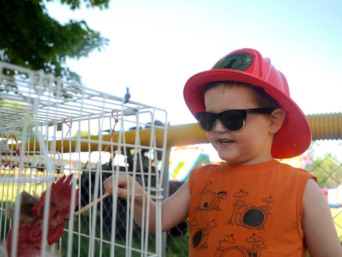 Kai Schmidt, 4, tries to feed a chicken during Spunktacular Days in Avon Saturday.