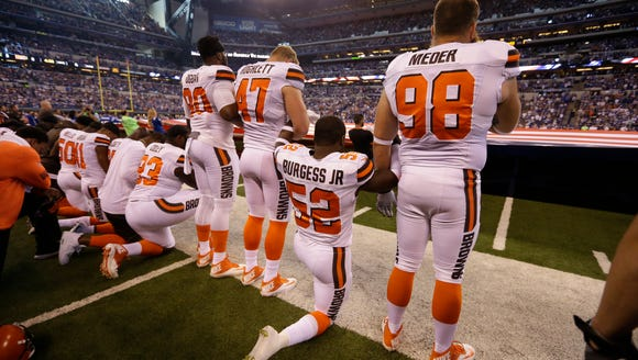 Members of the Cleveland Browns take a knee during