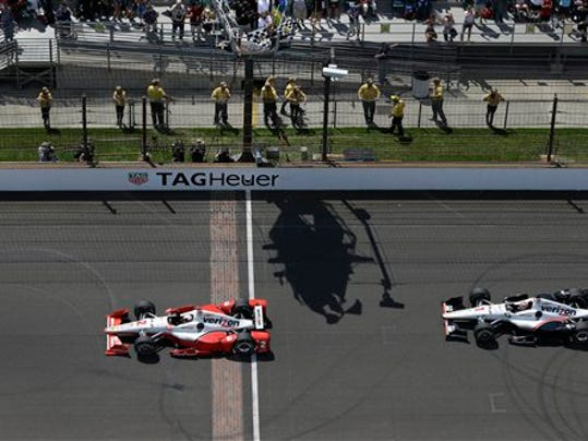 Juan Pablo Montoya, of Colombia, takes the checkered flags ahead of Will Power, of Australia, to win the 99th running of the Indianapolis 500 auto race at Indianapolis Motor Speedway in Indianapolis, Sunday, May 24, 2015.