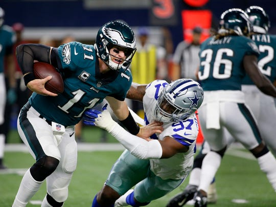 Carson Wentz staves off Taco Charlton of the Cowboys during a game Nov. 19 in Arlington.