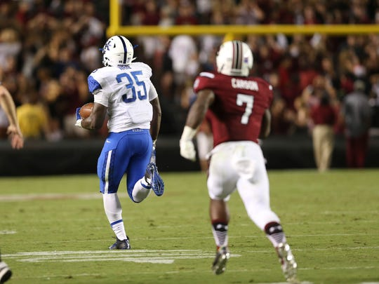 Kentucky Wildcats defensive end Denzil Ware (35) is chased by South Carolina's Shon Carson (7) as he returns a fumble for two points after South Carolina fumbled on a two-point conversion-attempt in the second half of an NCAA college football game Saturday, Sept. 12, 2015, in Columbia, S.C. Kentucky won 26-22. (AP Photo/John Bazemore)