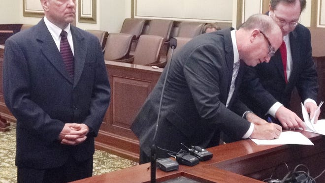 John Fussner, left, pleaded guilty Thursday in a criminal case also involving Mason lawmaker Peter Beck. Fussner's attorney, Mike Allen and Joshua Engel, far right, prepare paperwork.